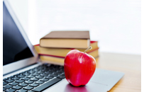 An apple on top of laptop and books.